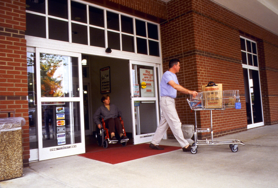 In this 1996 image, a wheelchair-seated woman was seen as she was about to pass through an automatic doorway of a grocery store through whic
