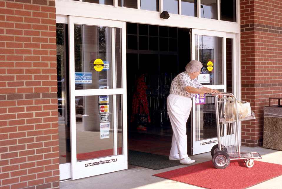 This 1996 image depicted a woman departing a grocery store while pushing a grocery cart. Due to the nature of the act of pushing the cart, h