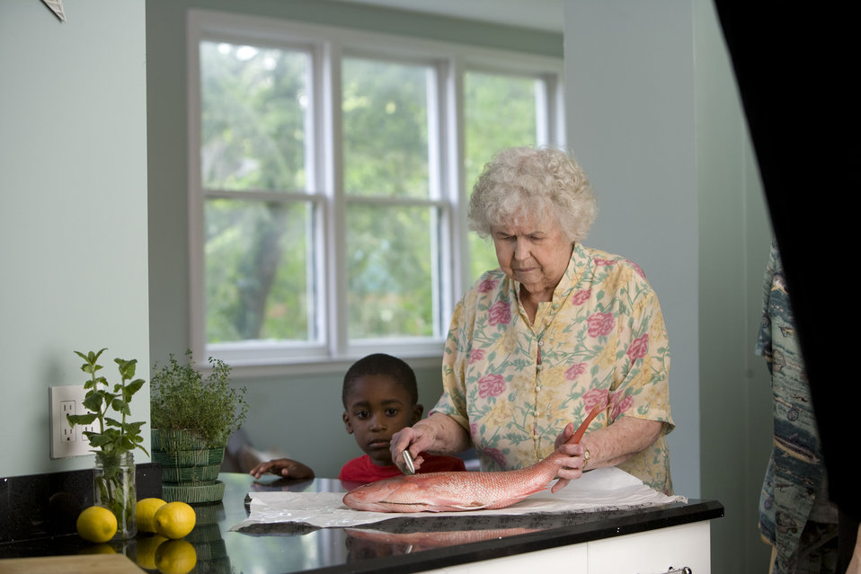 Here, an elderly woman was in the process of preparing a fresh fish on her clean kitchen counter, while a young African-American boy watched