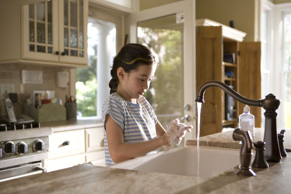 This young girl was shown in the process of properly washing her hands at her kitchen sink, briskly rubbing her soapy hands together under f