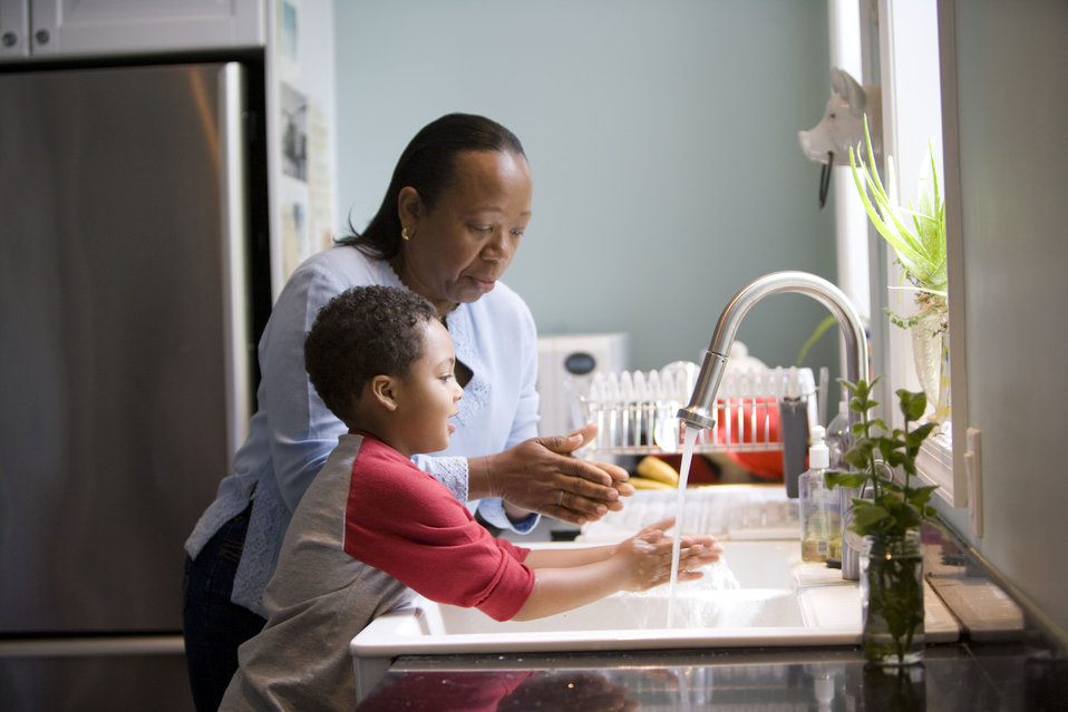 This African-American mother was shown in the process of teaching her young son how to properly wash his hands at their kitchen sink, briskl