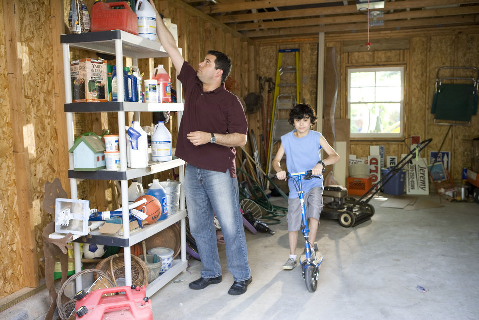 Here we see a father organizing his garage contents, while his son was about to embark on a scooter ride.