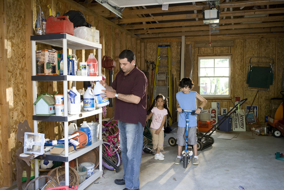 Here we see a father organizing his garage contents, while two of his children entertained themselves with some of the playthings stored ins