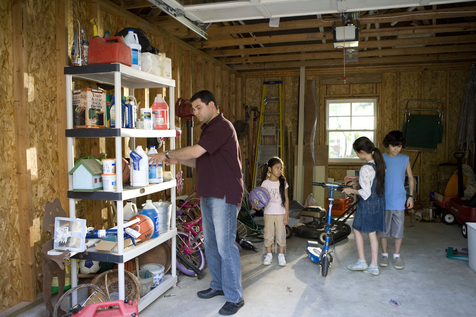 Here we see a father organizing his garage contents, while his children entertained themselves with some of the playthings stored inside.