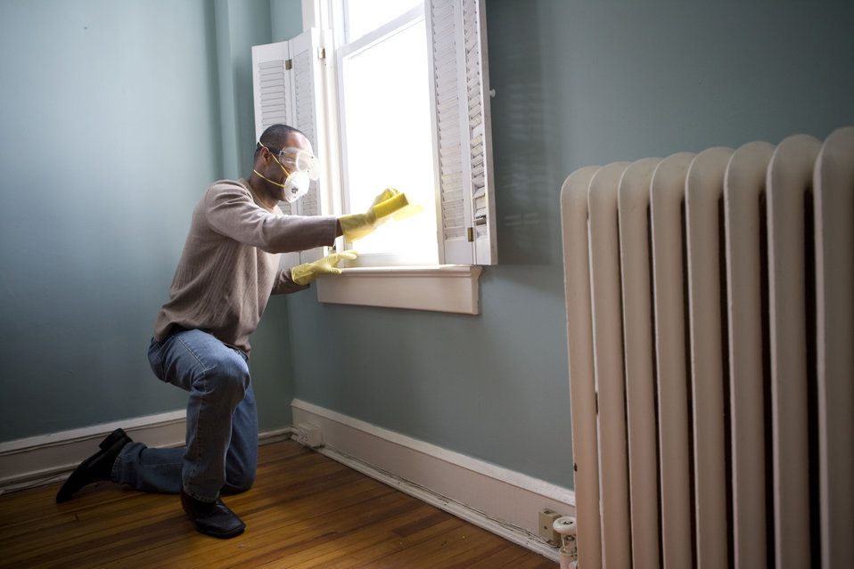 When renovating a home, you should use a damp sponge or cloth to clean dust collected on a window sill, as the dust may contain asbestos or