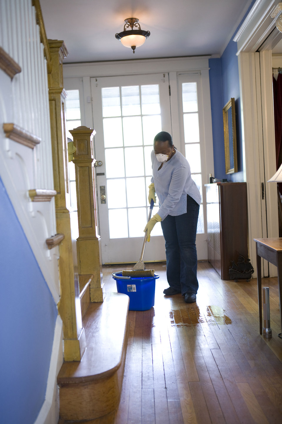 This African-American woman was in the process of damp-mopping her home's entrance way. When renovating a home, you should use a damp mop or