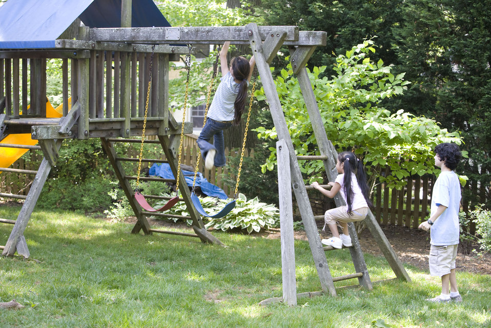 Children love playing outside, and these children were thoroughly enjoying their wooden swing set, and all were having fun in the fresh outd