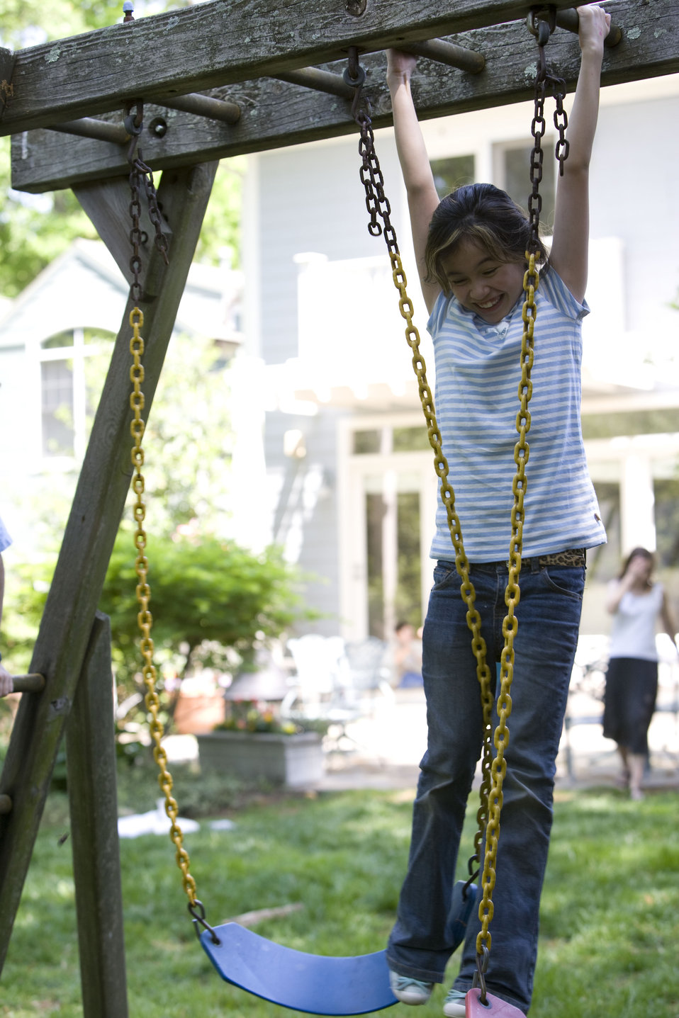 This young girl was playing outside on her backyard swing set, while in the background her mother could be seen calling out to her, probably