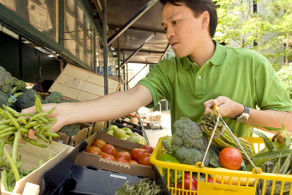 This photograph depicts a man shopping at a mobile produce market, making healthy food choices from an array of fresh fruits and vegetables.
