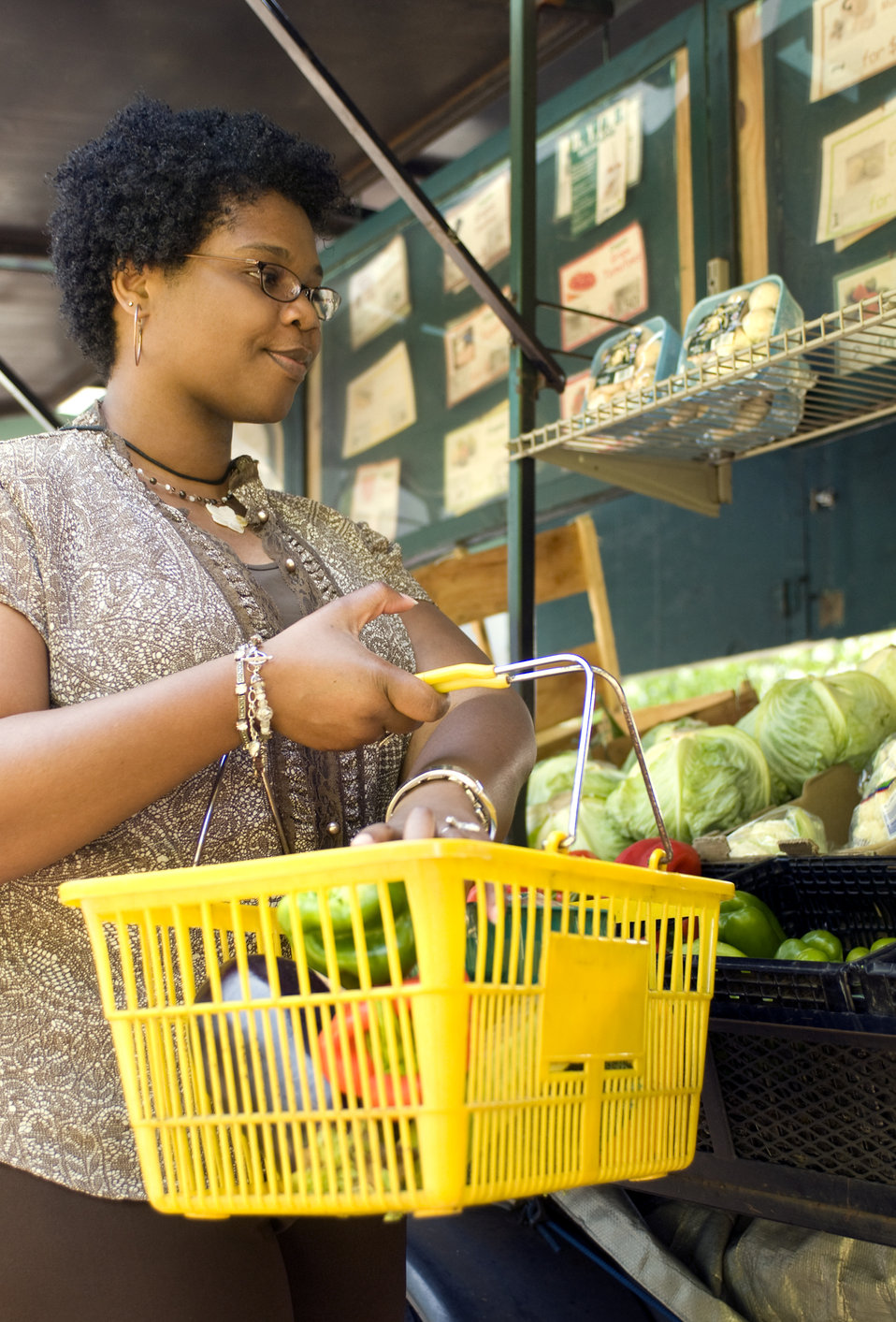 This photograph depicts a woman shopping at a mobile produce market, making healthy food choices from an array of fresh fruits and vegetable
