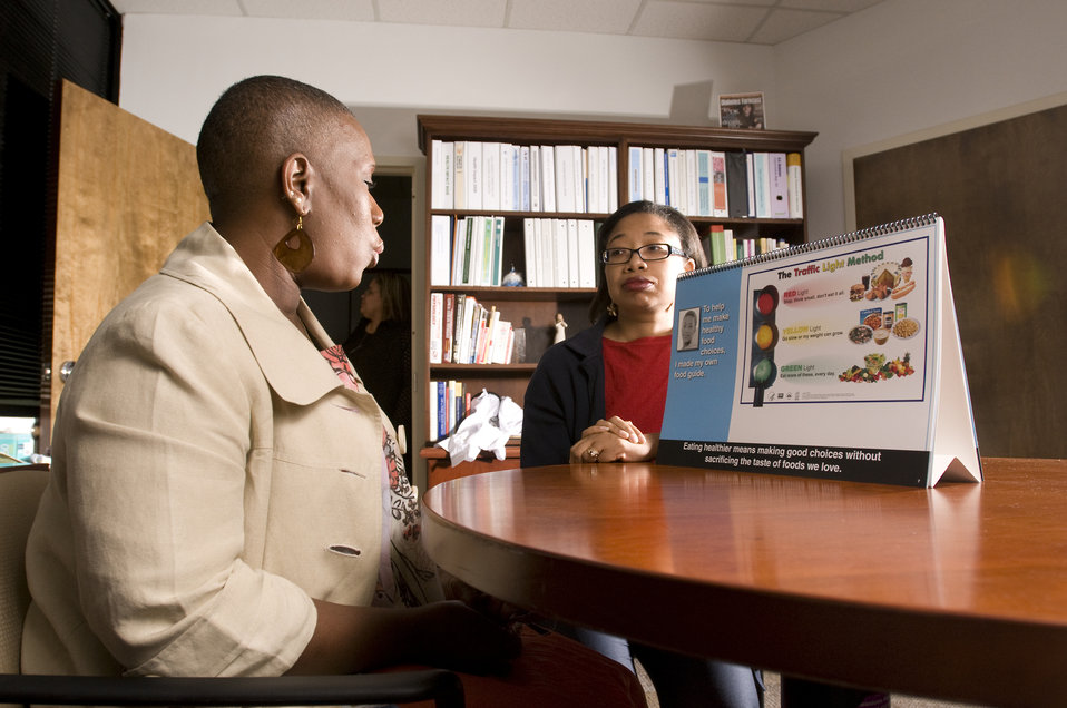 This image depicts a person with diabetes in the foreground listening to a community health worker familiar with the necessary diet needed t