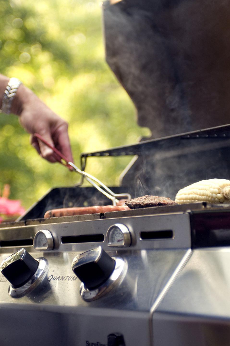 This image shows the grill, being used to thoroughly cook some hamburgers and hotdogs during an outdoor cookout.