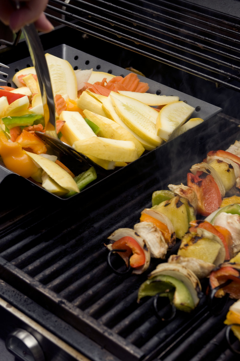 This image depicts freshly-prepared kabobs (Lt), which had been set atop an outdoor stainless steel gas grill, and were cooking. The skewers