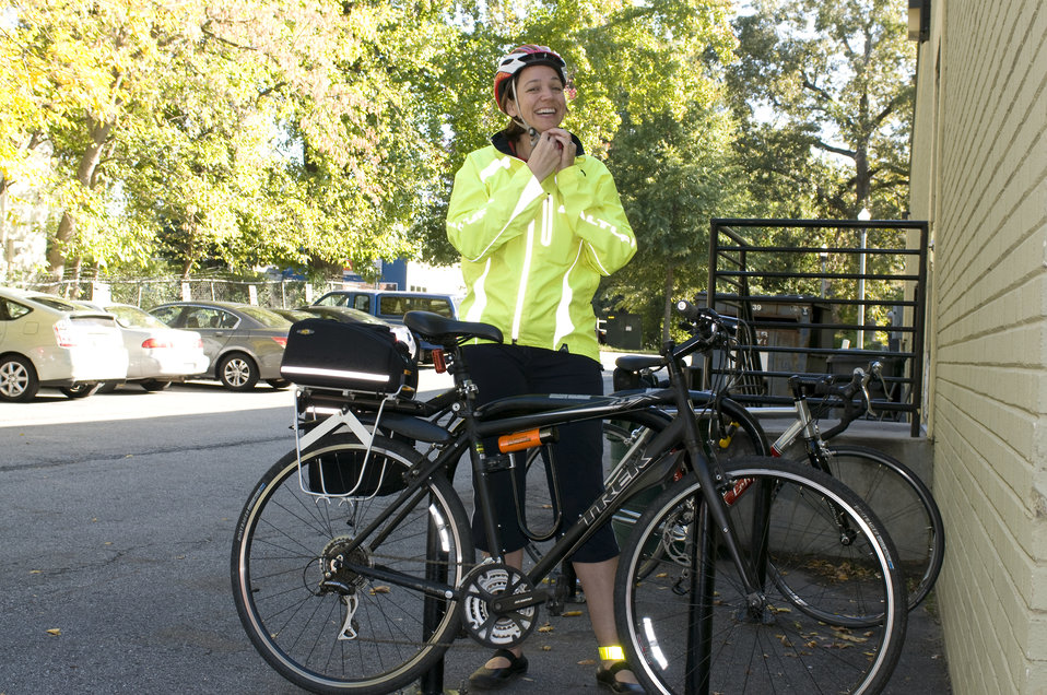 This photograph depicts a smiling female bicyclist, who was about to embark on a bicycle ride, but before which was in the process of adjust