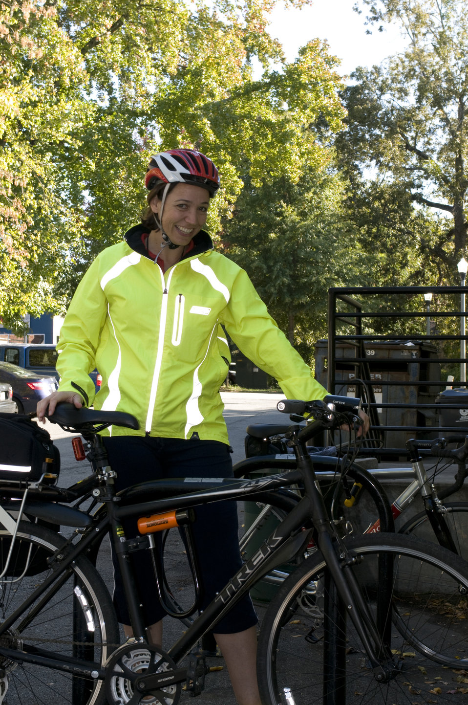 This photograph depicts a smiling female bicyclist, who was about to embark on a bicycle ride. Note the brightly-colored windbreaker she was