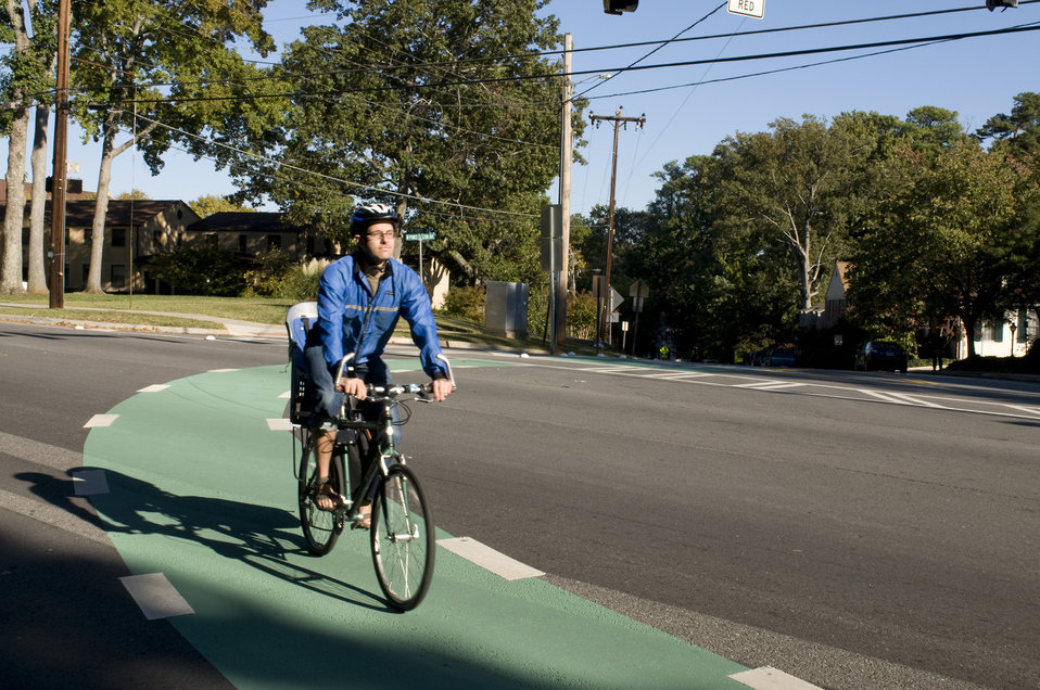This photograph depicts a male bicyclist, who was riding his bicycle on a sunny Georgia morning. Note the brightly-colored windbreaker she w