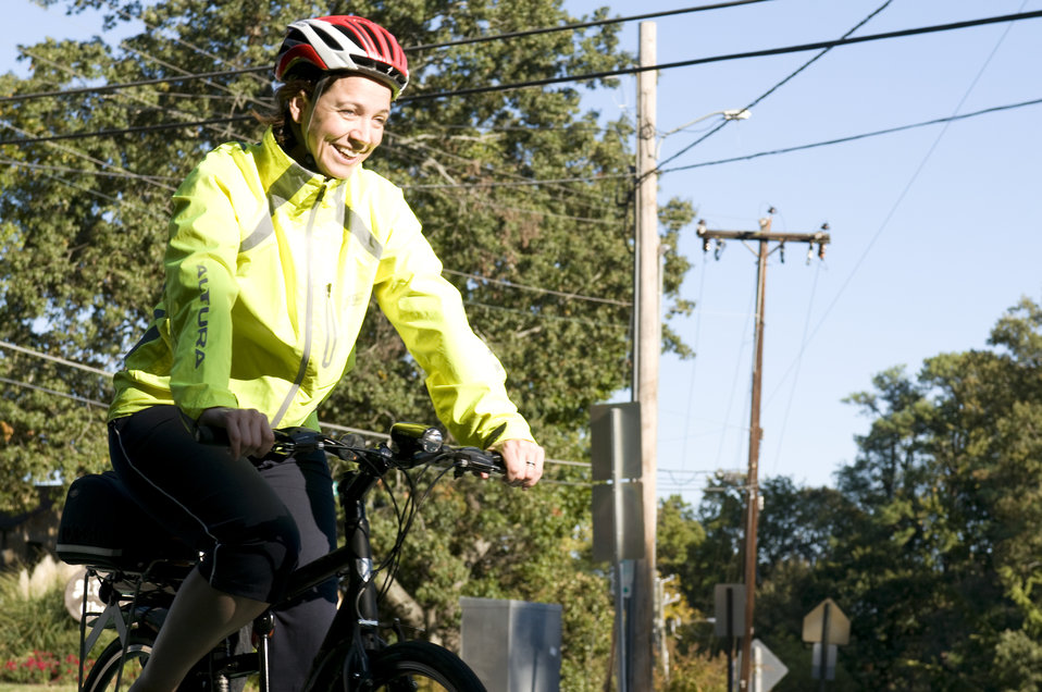This photograph depicts a smiling female bicyclist, who was riding her bicycle on a sunny Georgia morning. Note the brightly-colored windbre