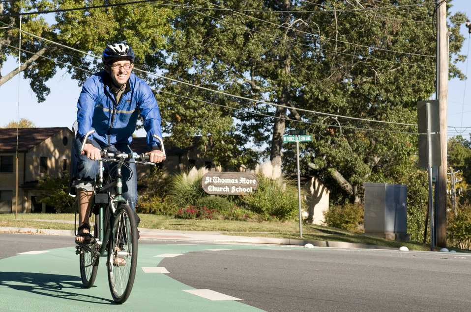 This photograph depicts a smiling male bicyclist, who was riding his bicycle on a sunny Georgia morning. Note the brightly-colored windbreak