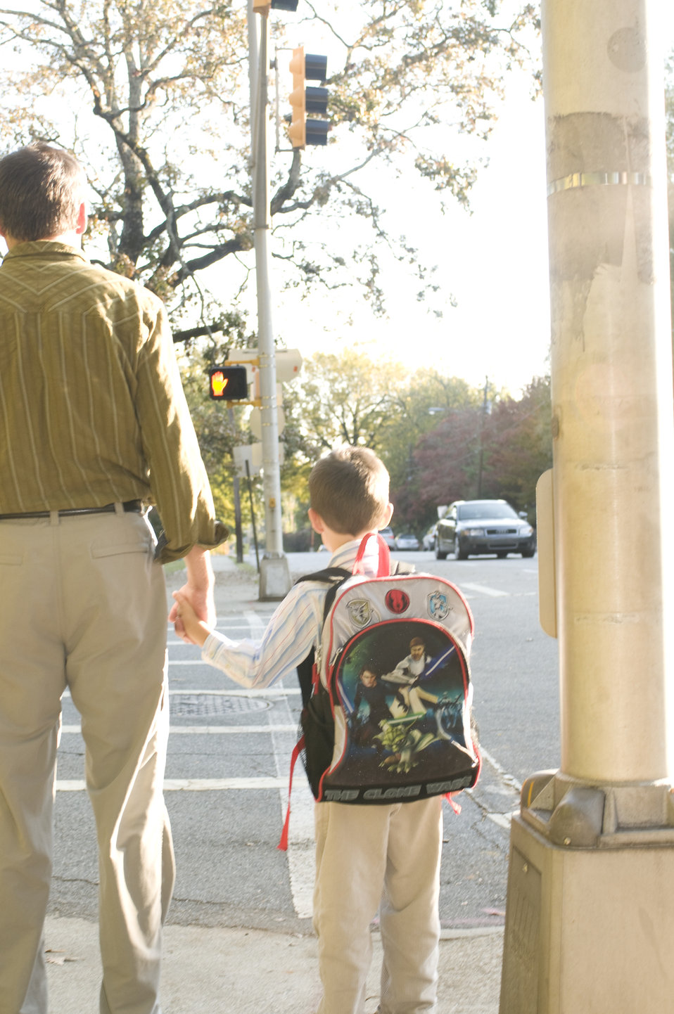 This father was shown walking on a Georgian city street, while to his left, he was holding hands with his young son. They had paused at an i