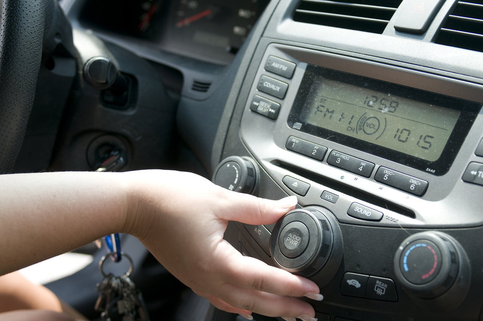 This image depicts the hand of a teenage female driver adjusting the volume of her car radio, while seated behind the wheel of her automobil