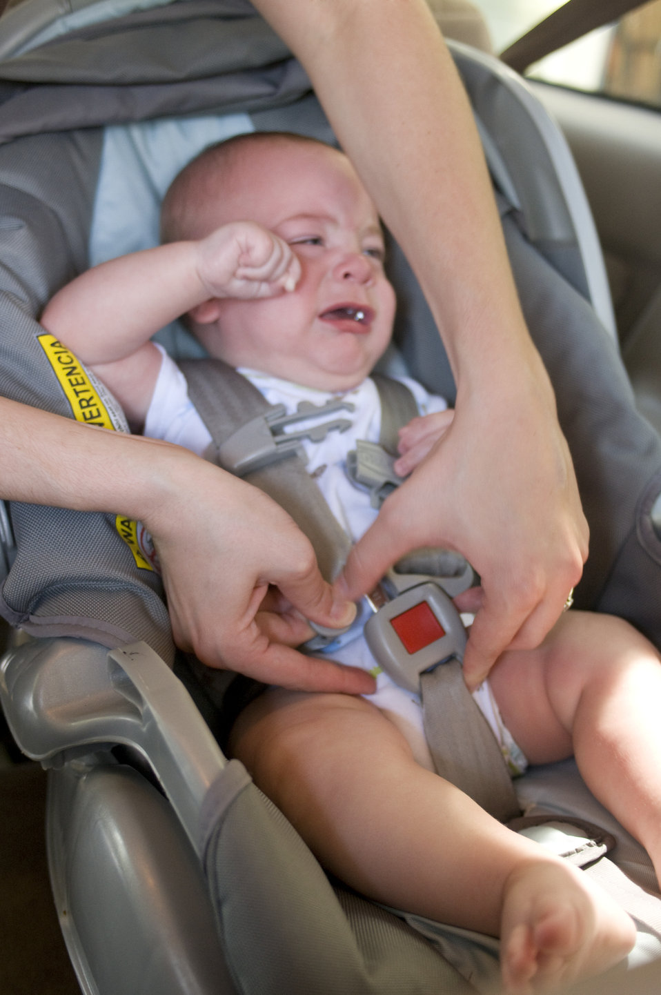 This image depicts a mother in the process of securing her infant child into a back seat-located child safety seat. At this point of the pro