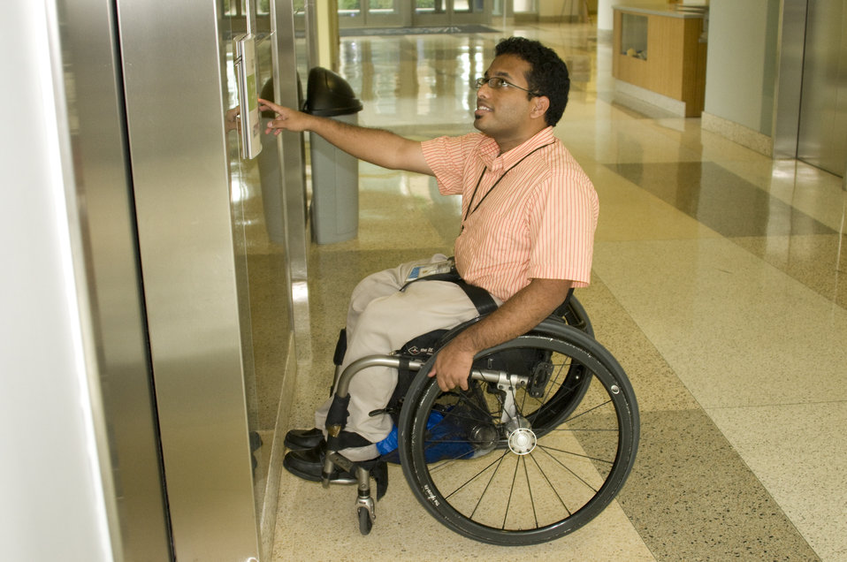 Seated in a wheelchair, the man depicted here was in the process of hailing an elevator from the first floor of one of the Centers for Disea
