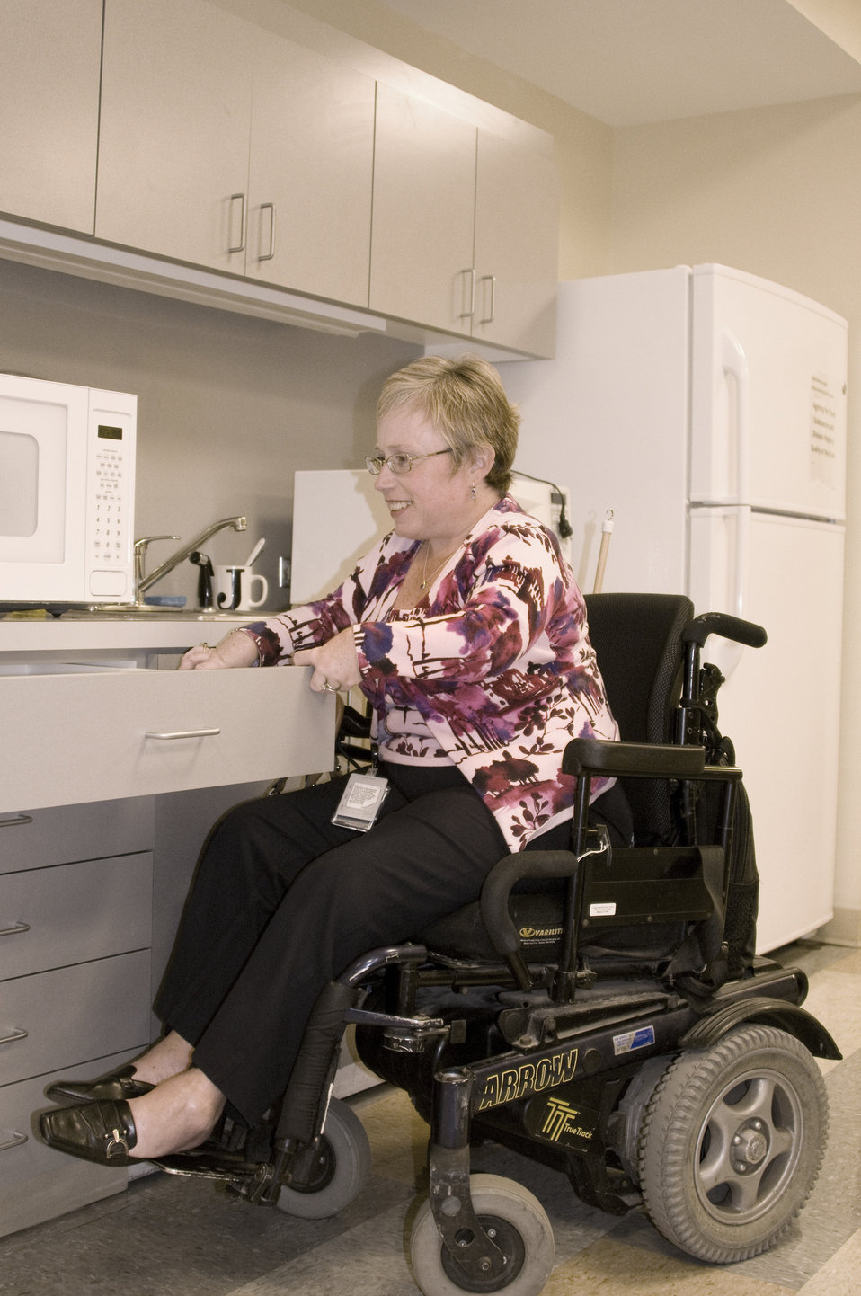 This woman who was seated in her wheelchair, was photographed in this kitchen setting while opening a cabinet drawer. Note that the height o