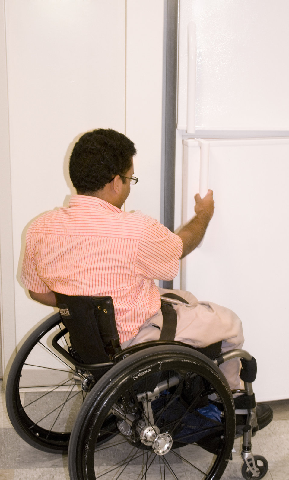 This man who was seated in his wheelchair, was photographed in this kitchen setting while opening the refrigerator's door. Note that the hei