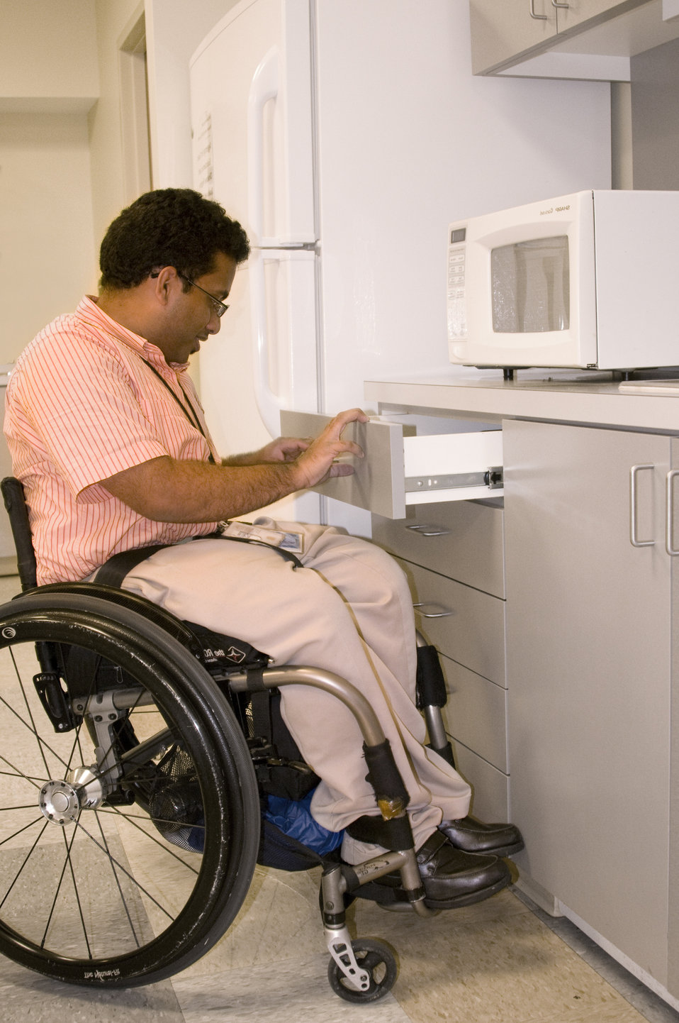 This man who was seated in his wheelchair, was photographed in this kitchen setting while opening a cabinet drawer. Note that the height of