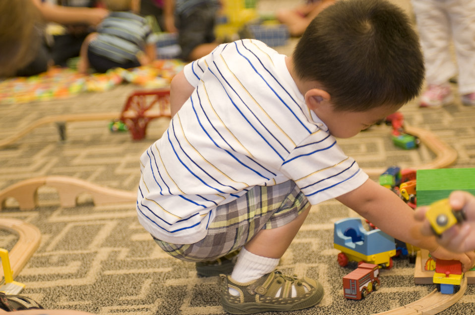 While in a daycare setting, this young boy was entertaining himself by playing with a small wooden toy car set, pushing the little cars alon