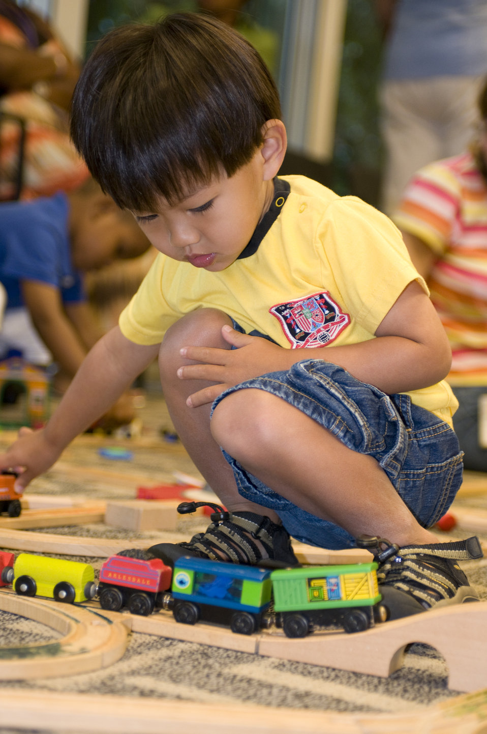 While in a daycare setting, this young boy was playing with a small wooden train set, pushing the little train cars along the grooved wooden