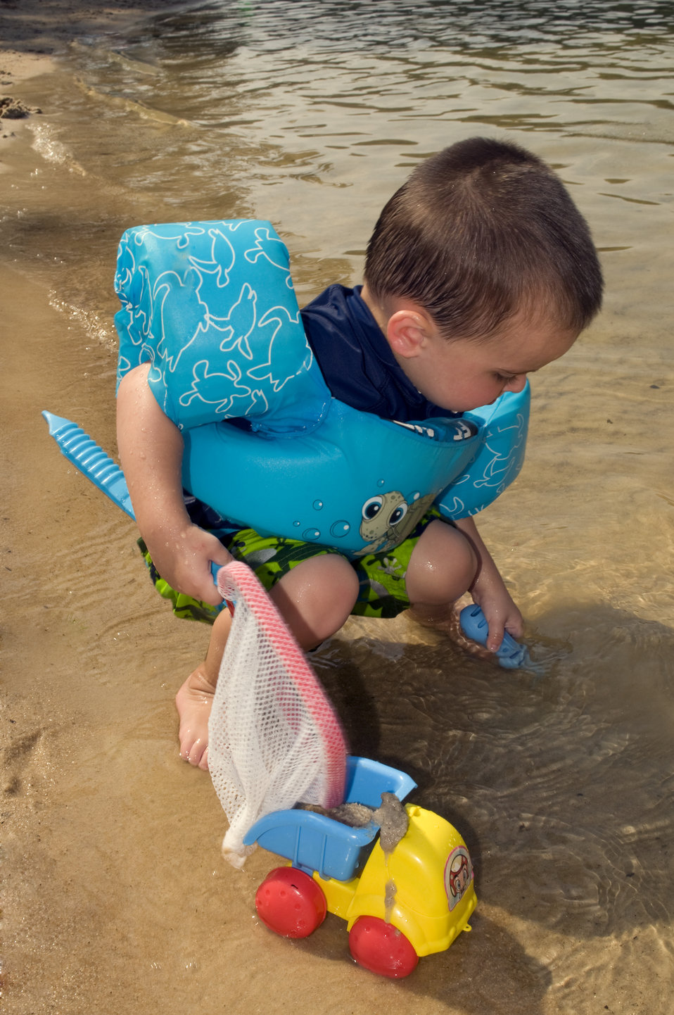 This young boy was kneeling at the water's edge holding a toy fishnet with his right hand, and a plastic strainer with his left, which he wa