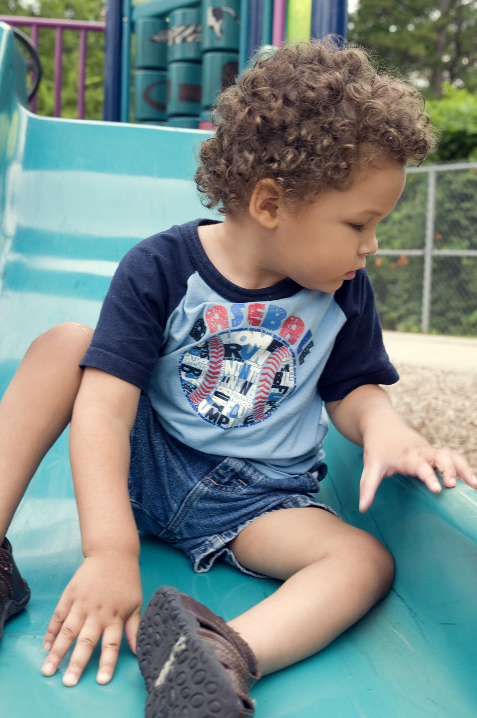 The young boy pictured here was seated on a slide at a community playground, and was wearing a darkly-colored t-shirt and denim shorts, both