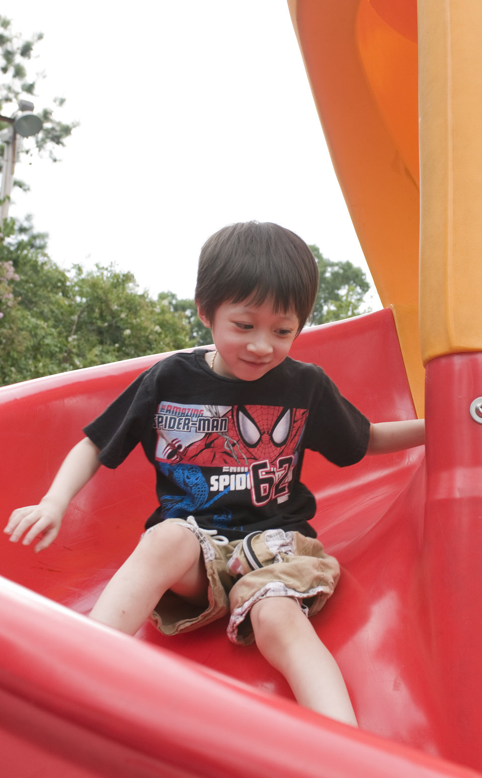 Under the watchful eye of his mother, this young boy was taking a trip down a bright red slide at a neighborhood playground. Note that he wa