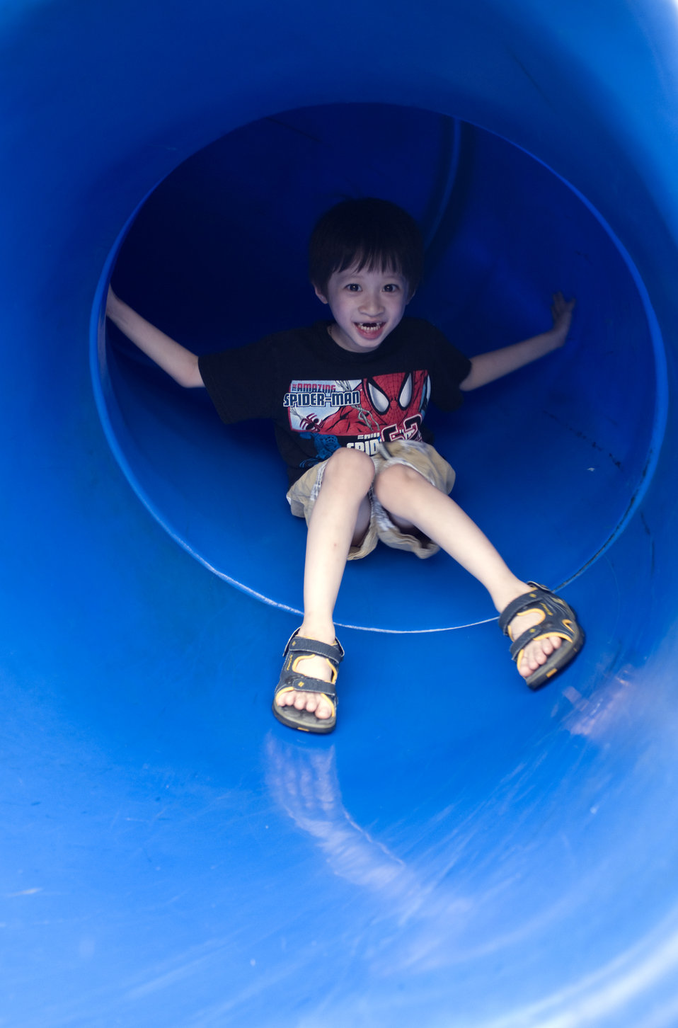 Under the watchful eye of his mother, this young boy was taking a trip down a bright blue slide at a neighborhood playground. Note that he w