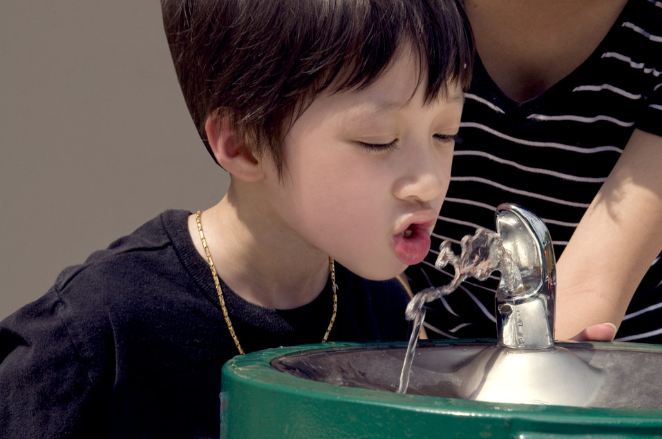 With his mother at his side, this young boy had taken a short break during a day of play at a local playground to take a drink of cool water