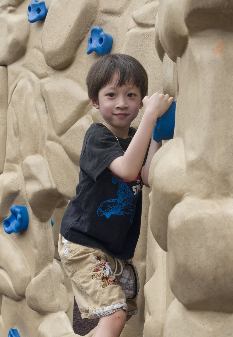 A young boy climbing a rock wall