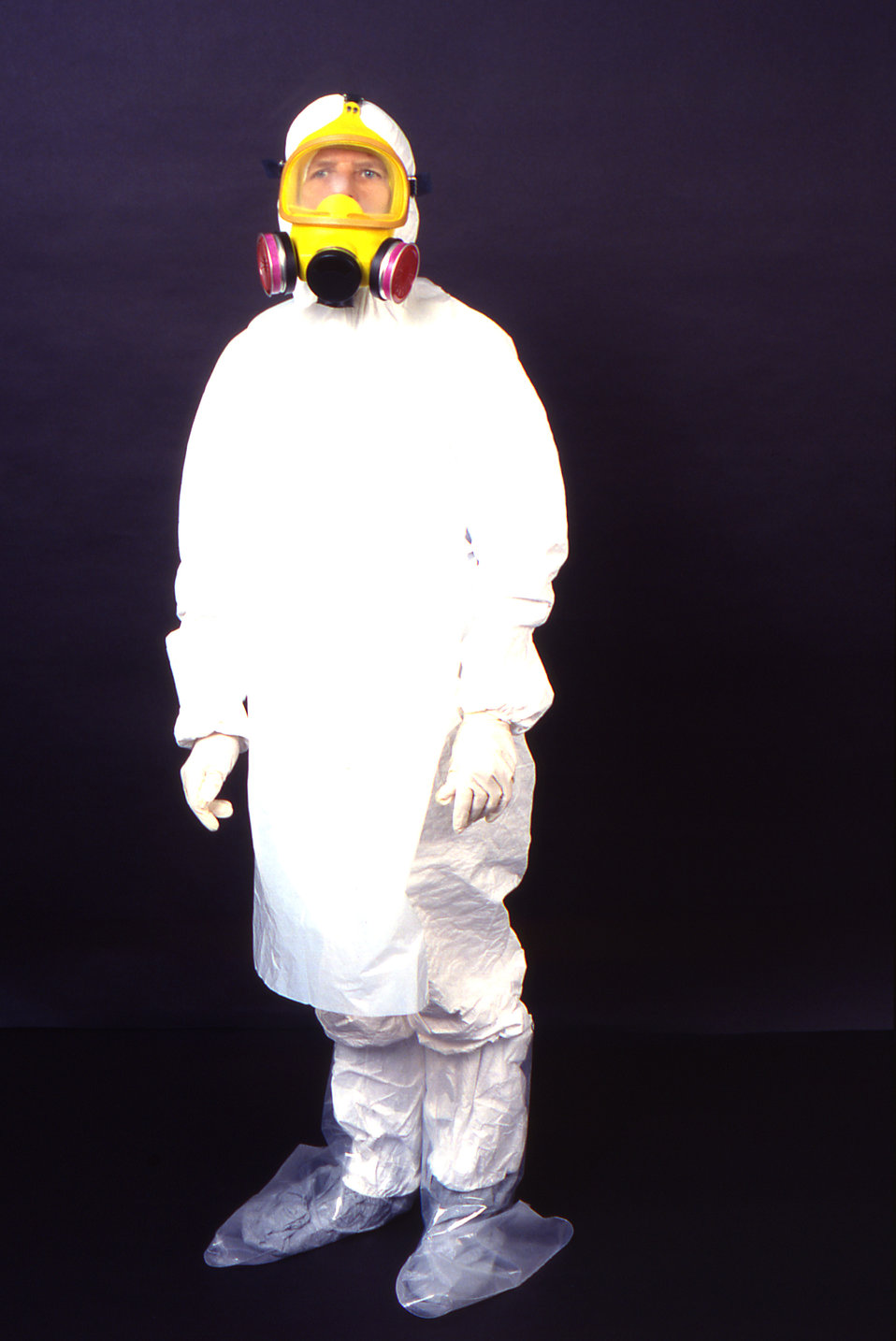 This 1995 image depicts a left anterior-oblique view of a laboratory technician wearing garments usually worn by field techs including a dis