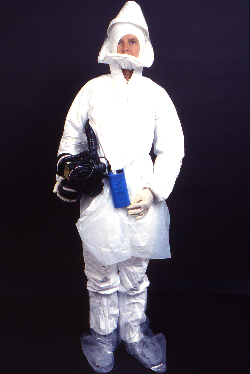 This 1995 image depicts an anterior view of a laboratory technician wearing garments usually worn by field techs including a disposable whit