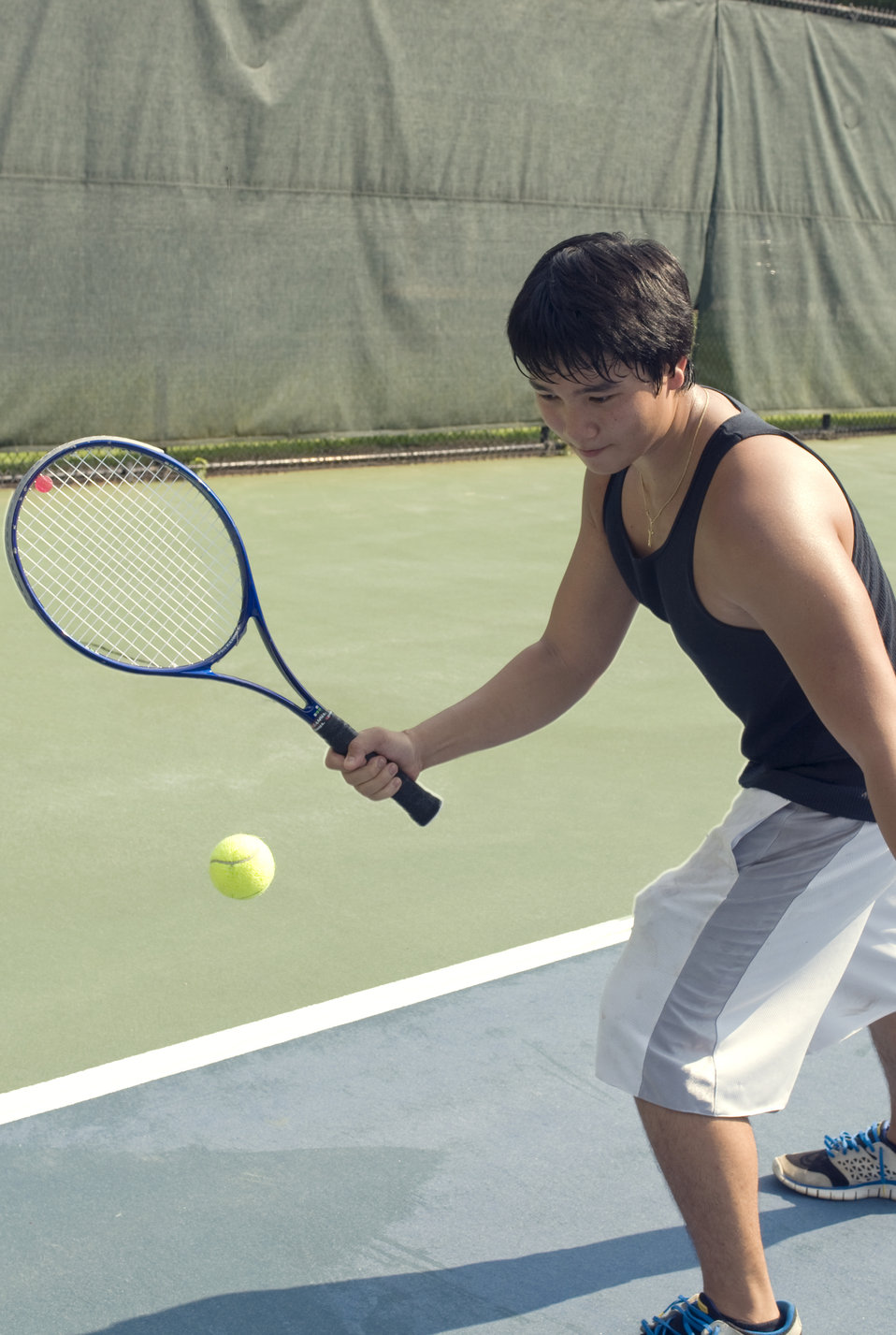 Right hand holding a tennis racket, this young man was playing a game of tennis on the court. Wearing a darkly-colored tank top, loose-fitti
