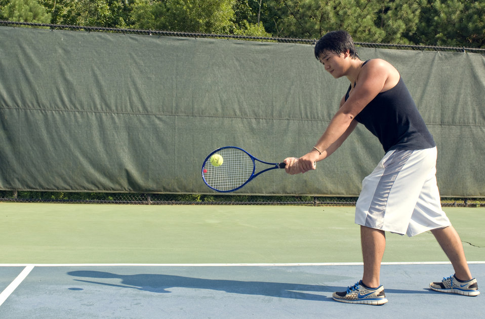 Caught in a mid-forehand swing, this young man was playing a game of tennis on the court. Wearing a darkly-colored tank top, loose-fitting s