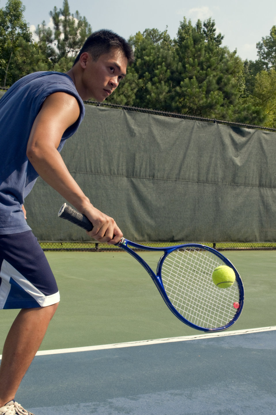 Caught in a mid-backhand swing, this young man was playing a game of tennis on the court. Wearing a darkly-colored tank top, loose-fitting s