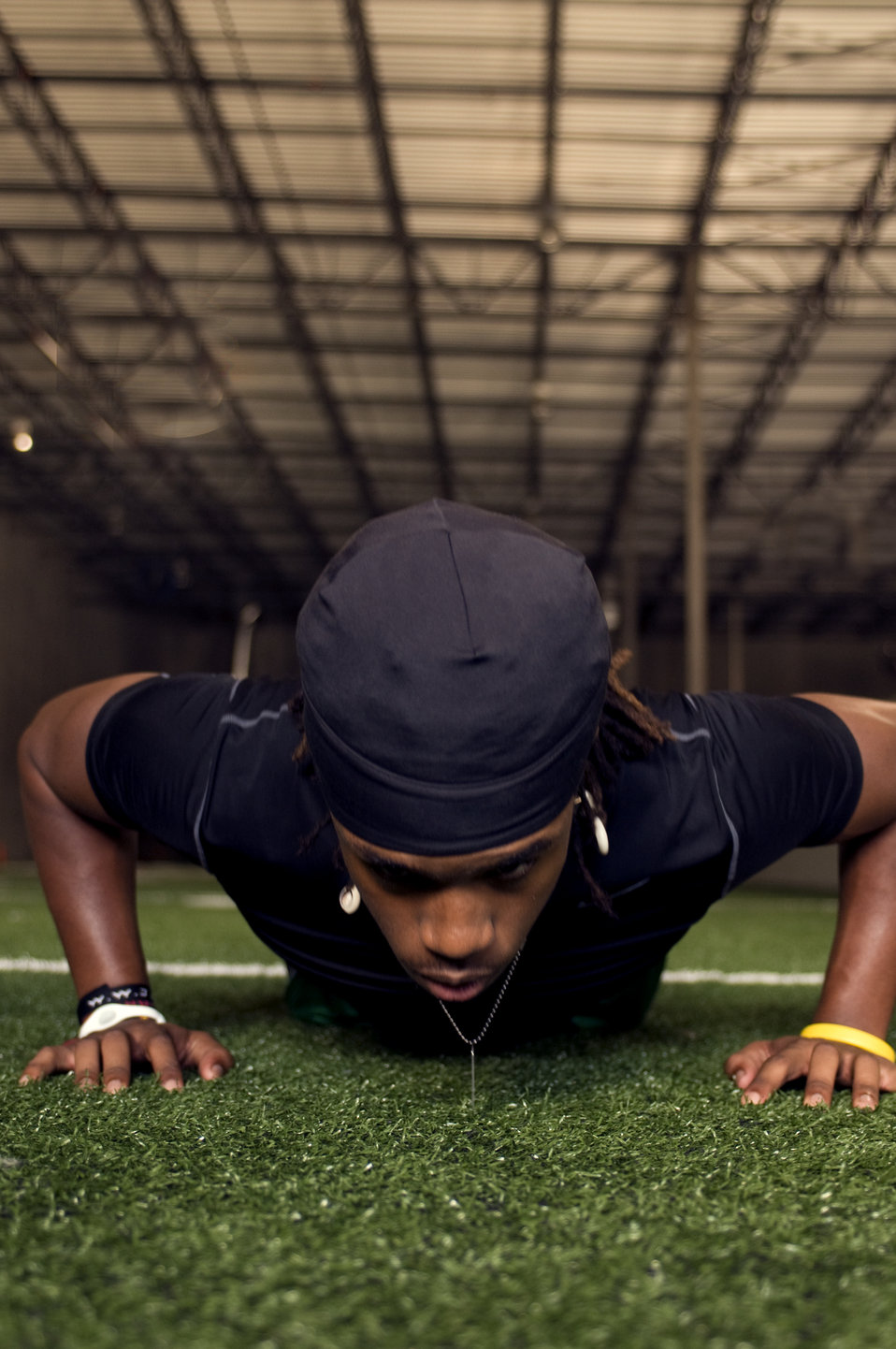 This young man was performing push-ups on an indoor practice field's artificial grass surface. At this point of his activity, he was at the