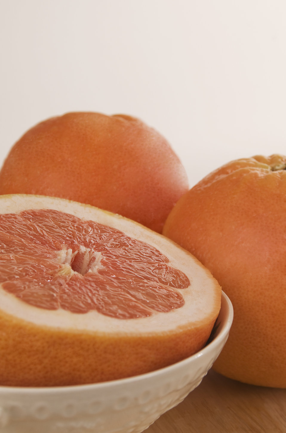 This image depicts a clean wooden tabletop, atop which two whole grapefruit, and a white ceramic bowl containing a half of one of these frui
