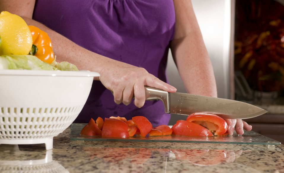 Here we see a woman in a kitchen setting photographed in the process of preparing a number of just-washed red bell peppers, atop a clean gla