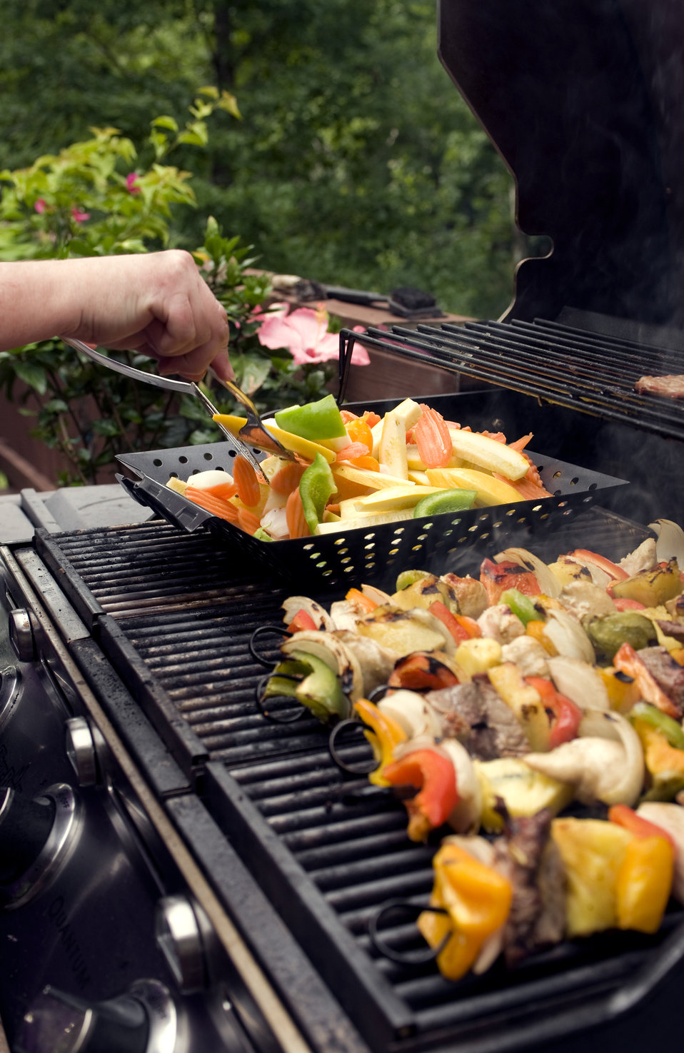 This image depicts four freshly-prepared kabobs, which had been set atop an outdoor stainless steel gas grill, and were cooking. The skewers