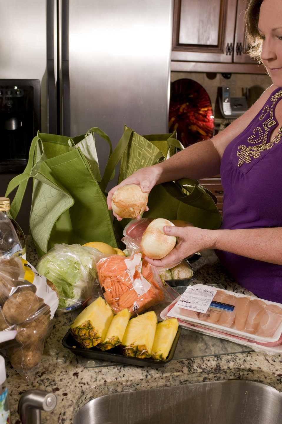 Holding two sweet onions, the woman pictured in this photograph was in the process of sorting through her cache of newly-purchased groceries