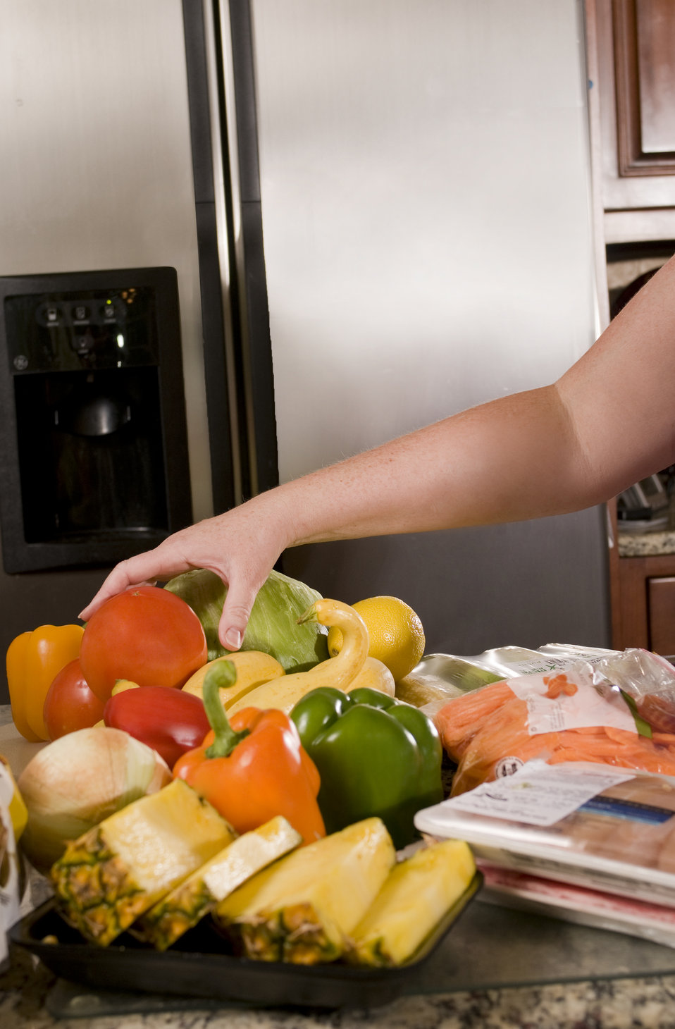 This image depicts a woman's arm reaching for a tomato amongst a cache of newly-purchased groceries atop her sink's countertop, The grocery