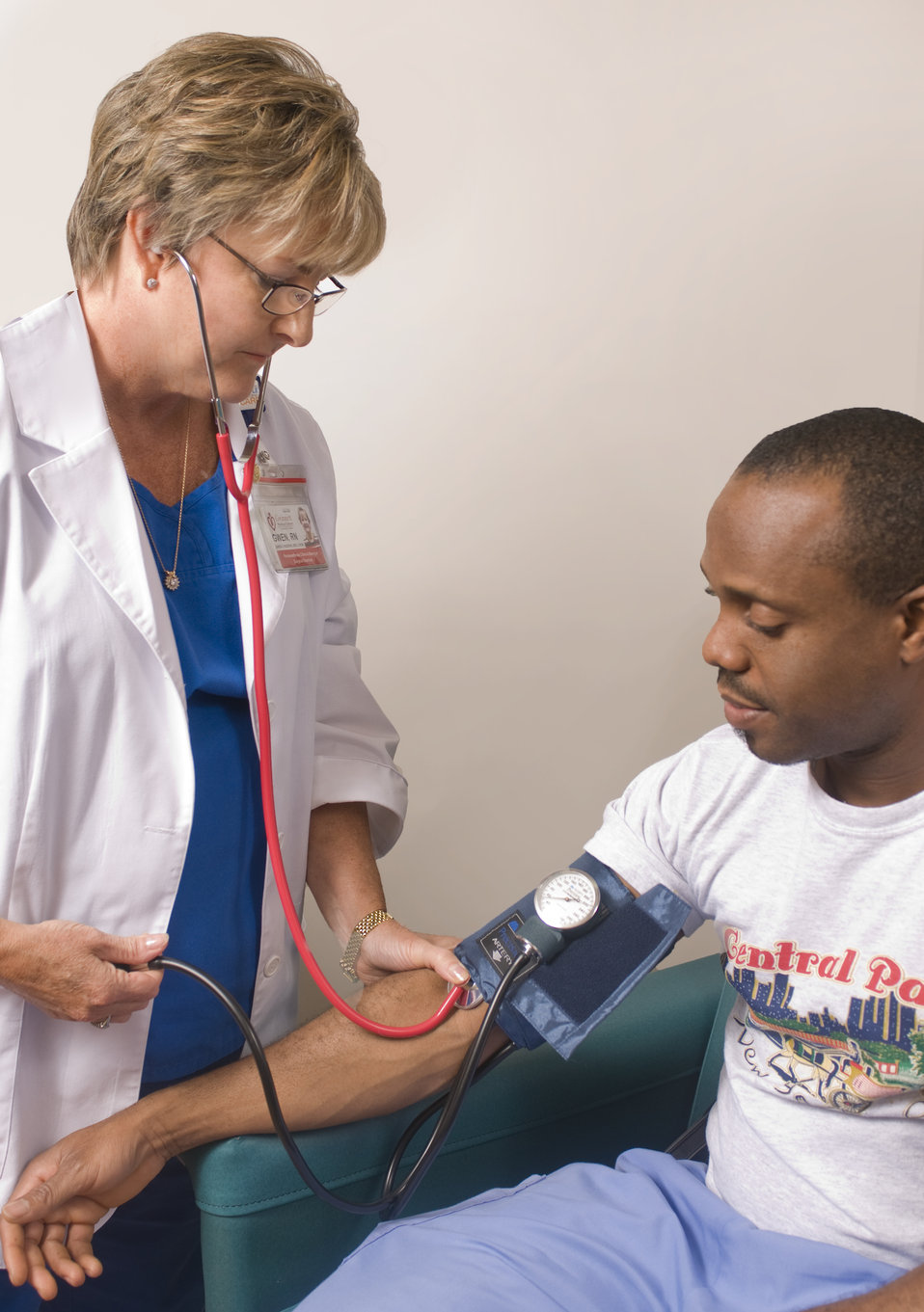 This image depicts a female clinician in the process of conducting a blood pressure examination upon a seated male patient in a clinical set