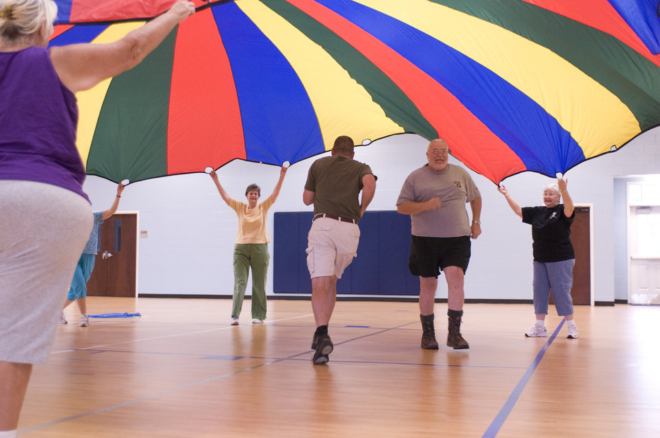 The older individuals pictured here on the wooden floor of an indoor basketball court, were participating in an exercise class consisting of